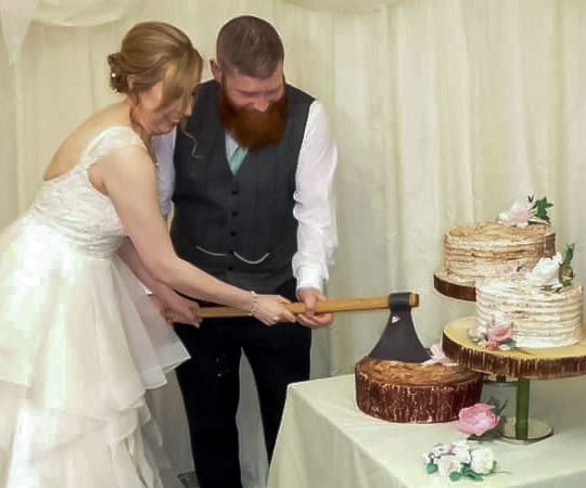 A couple cutting their wedding cake with our Scottish Robert the Bruce Axe